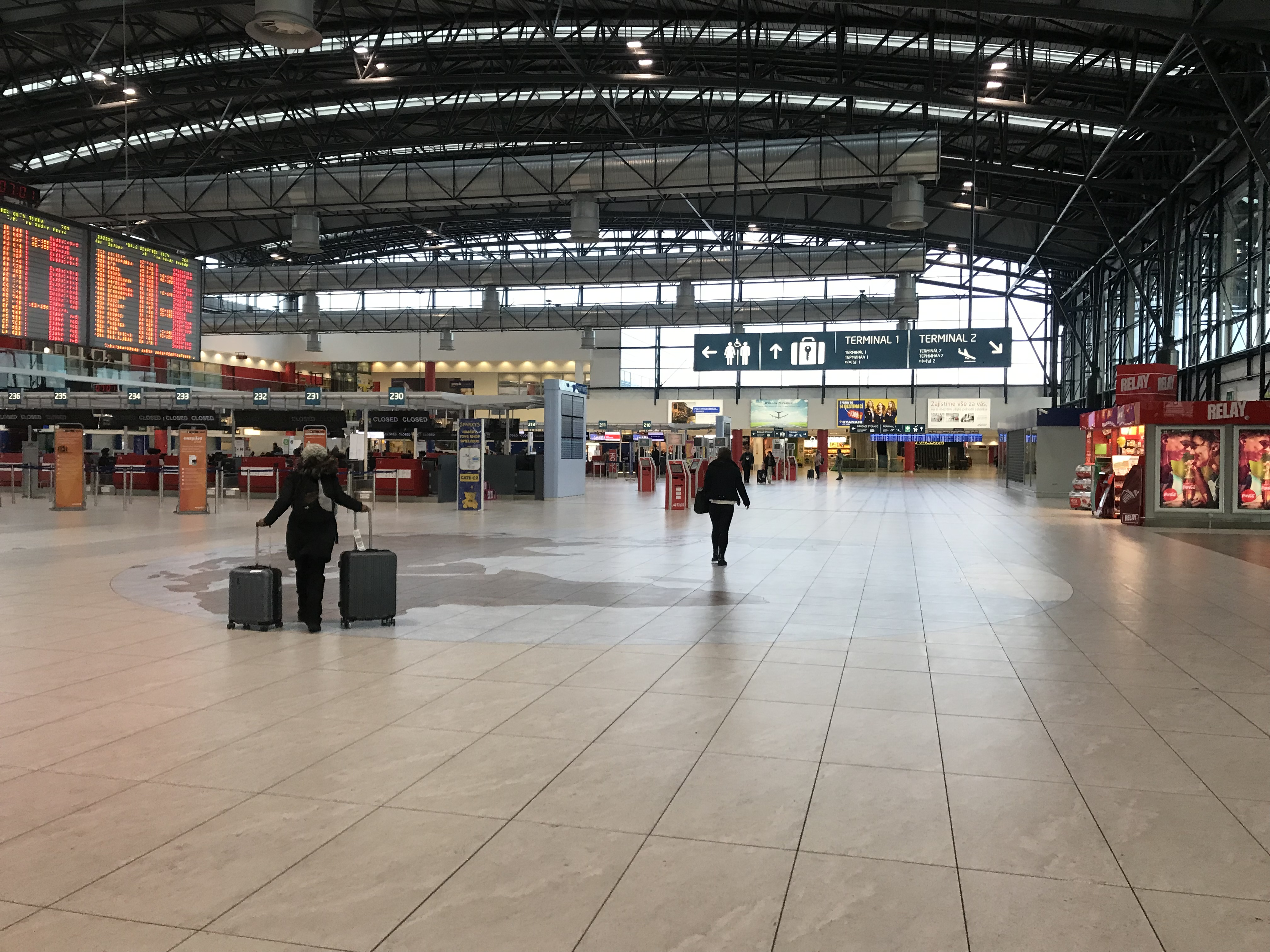 Inside the main hall of the Prague's airport. The airport has two terminals and there are clear signs guiding you to them.