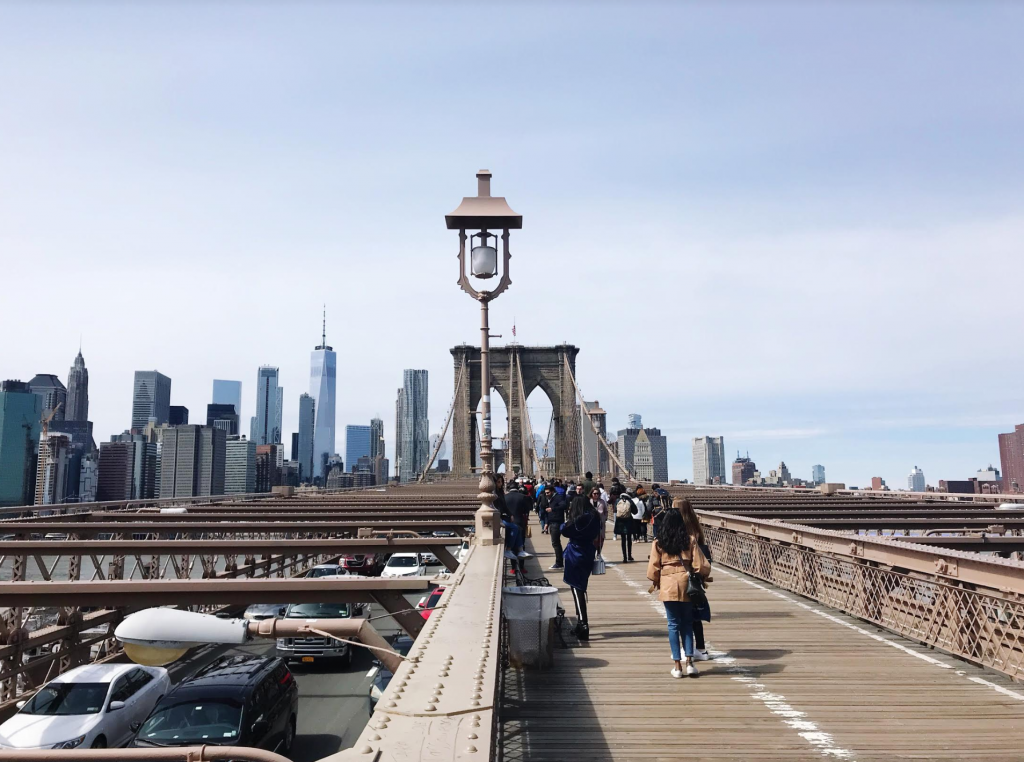 Brooklyn Bridge as a level for cars and pedestrians walk on the wooden floor on top of it.