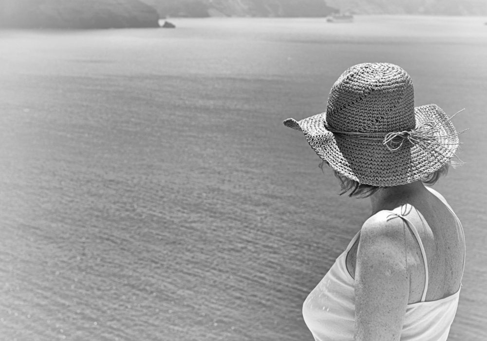 Lady in Santorini's hills, looking at the caldera